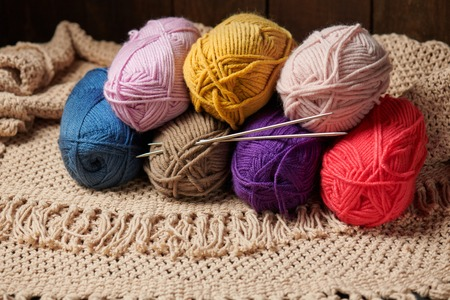 Balls of woolen thread for knitting on wooden background
