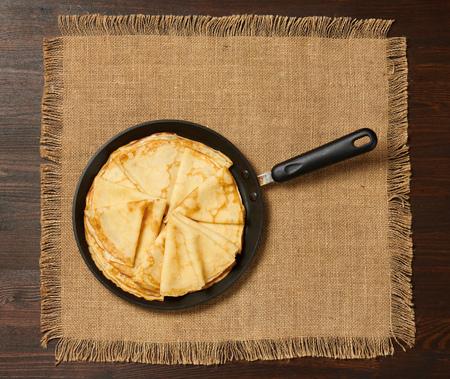 Crepe closeup, thin pancake on a frying pan, wood background