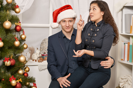 Romantic couple having fun - the girl is sitting on Santa, wants many gifts and makes wishes. Christmas tree with holiday decoration, new year theme Standard-Bild