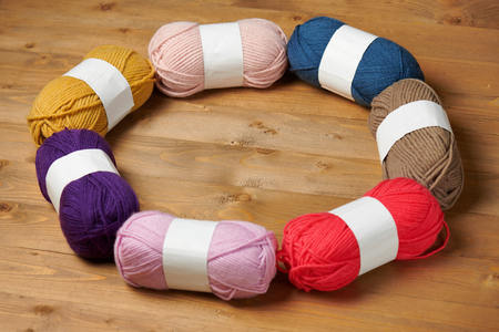 colorful wool threads for knitting on wooden background