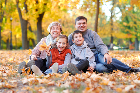 Happy family lies in autumn city park on fallen leaves. Children and parents posing, smiling, playing and having fun. Bright yellow trees.