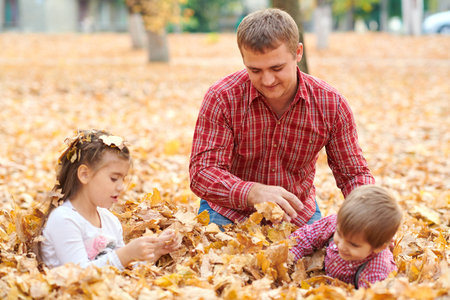 Father and children are lying on yellow leaves and having fun in autumn city park. They posing, smiling, playing. Bright yellow trees.