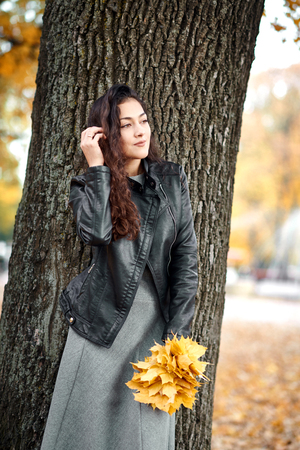 Woman with yellow leaves stand near big tree in autumn city park. 写真素材