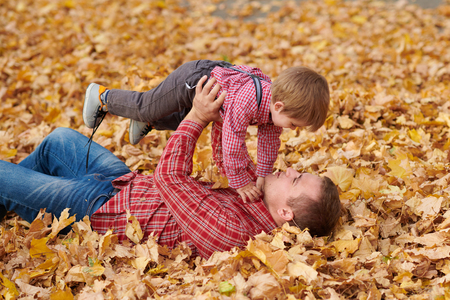 Father and son are lying on yellow leaves and having fun in autumn city park. They posing, smiling, playing. Bright yellow trees.