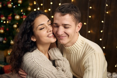 young couple is in christmas lights and decoration, dressed in white, fir tree on dark wooden background, winter holiday concept Imagens