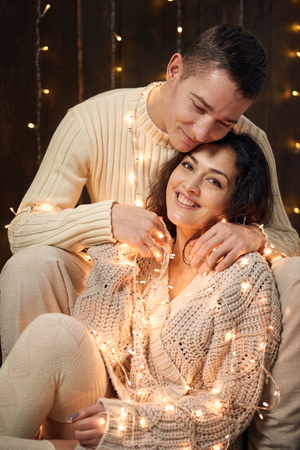 young couple is in christmas decoration and lights, fir tree on dark wooden background, new year holiday concept Reklamní fotografie