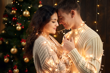 young couple is in christmas decoration and lights, fir tree on dark wooden background, new year holiday concept Banco de Imagens