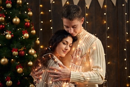 young couple is in christmas decoration and lights, fir tree on dark wooden background, new year holiday concept 版權商用圖片