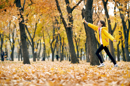 Happy teen girl is running in autumn park with big maples leaf. Bright yellow leaves and trees.