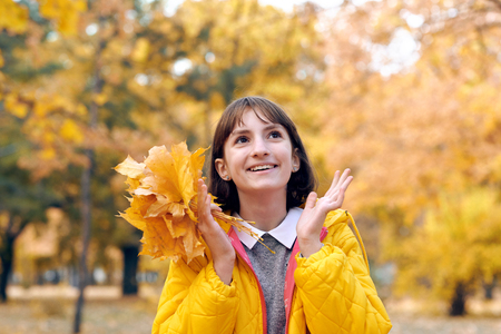 Teen girl is posing with bunch of maple's leaves in autumn park. Beautiful landscape at fall season.