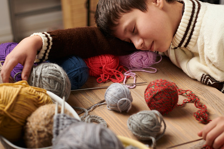 Child boy is learning to knit. He is dreaming and closing eyes. Colorful wool yarns are on the wooden table. Archivio Fotografico