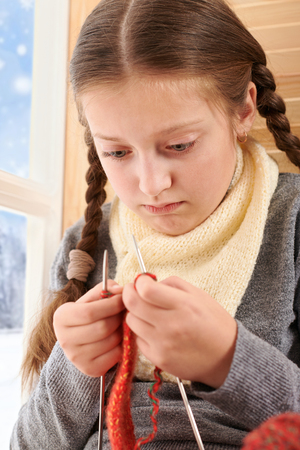 Child girl is sitting on a window sill with wool yarns and knitting. Beautiful view outside the window - sunny day in winter and snow. Stock Photo