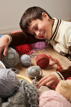 Child boy is learning to knit. He is dreaming and closing eyes. Colorful wool yarns are on the wooden table. 写真素材