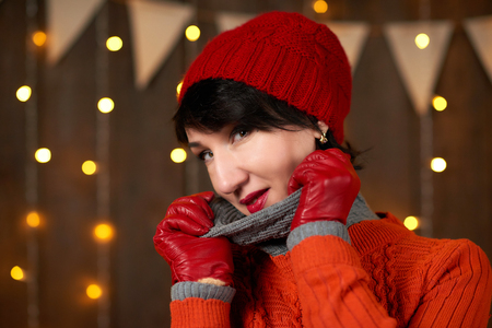 Beautiful woman is posing on dark wooden background, christmas lights and flags, holiday concept. Dressed in red knitted hat and sweater.