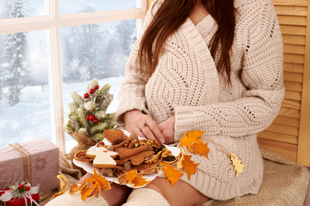 pregnant woman sitting near the window, beautiful winter landscape with snowy forest is outside the window, christmas decoration Stock Photo