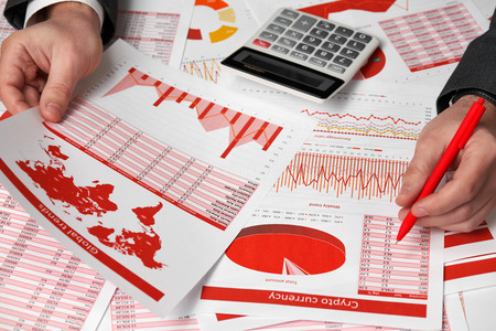 Businessman accountant using calculator for calculating cryptocurrency report on desk office. Business financial accounting concept. Red reports and graphs.