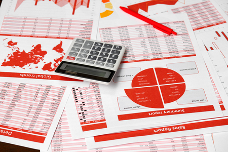 Red reports, graphs and calculator for calculating finance on desk office. Business financial accounting concept