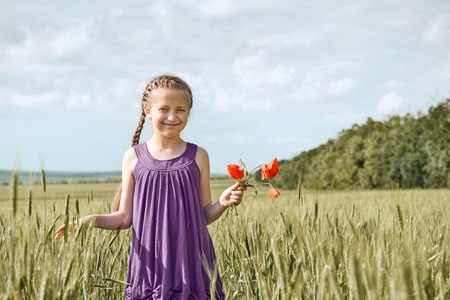 girl with red tulip flowers posing in the wheat field, bright sun, beautiful summer landscape