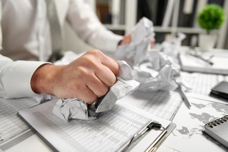 Boze zakenman heeft stress en problemen met slechte rapporten, hij breekt documenten en gooit ermee. Stockfoto