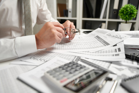 Businessman working at office and calculating finance, reads and writes reports. Business financial accounting concept. Banque d'images