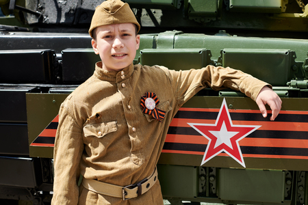 Boy dressed in Soviet military uniform during the second world war posing near army tank