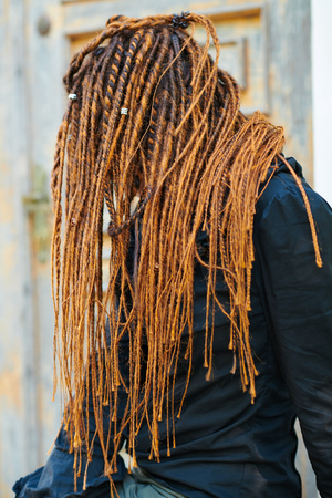 dreadlocks fashionable girl posing at old wooden door background. side view with no face visible Reklamní fotografie