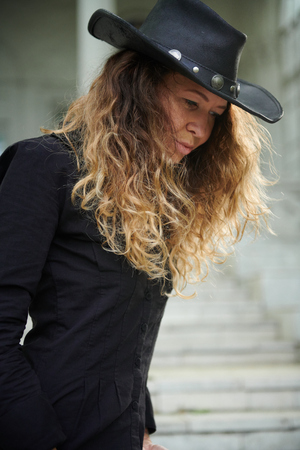 fashionable girl dressed in black shirt, hat and wide trousers posing near old white house