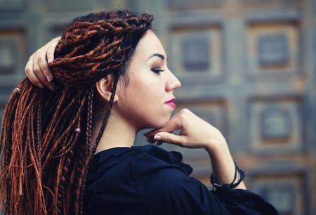 dreadlocks closeup, fashionable girl posing at old wooden door background Stock Photo