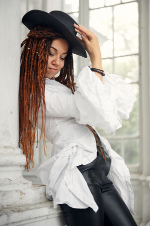 dreadlocks fashionable girl dressed in white shirt, black leather hat and trousers, posing in font of old palace Reklamní fotografie