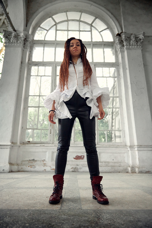 dreadlocks fashionable girl dressed in white shirt and black leather trousers posing in font of old big window