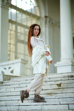dreadlocks fashionable girl dressed in white posing on old palace background