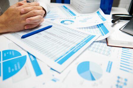Homme d'affaires travaillant et calculant, lit et écrit des rapports. Employé de bureau, gros plan de la table. Concept de comptabilité financière d'entreprise.