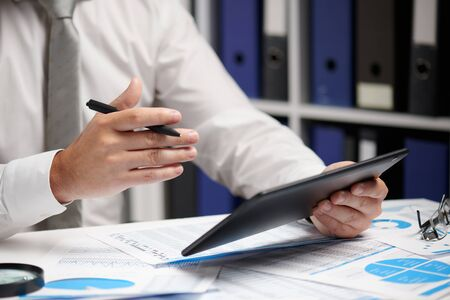 Uomo d'affari che lavora con tablet pc, calcola, legge e scrive rapporti. Impiegato d'ufficio, primo piano della tabella. Concetto di contabilità finanziaria aziendale.