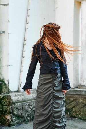 dreadlocks fashionable girl having fun and turns head fast Banco de Imagens