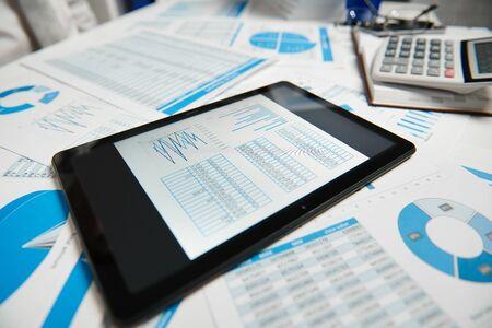 Kantoorwerkruimte voor bedrijven. Tablet-pc en rapporten. Tabel close-up. Zakelijke financiële boekhouding concept. Stockfoto