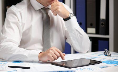 Uomo d'affari che lavora con tablet pc, calcola, legge e scrive rapporti. Impiegato d'ufficio, primo piano della tabella. Concetto di contabilità finanziaria aziendale. Archivio Fotografico