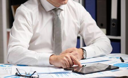 Homme d'affaires travaillant avec une tablette, calculant, lisant et écrivant des rapports. Employé de bureau, gros plan de la table. Concept de comptabilité financière d'entreprise.