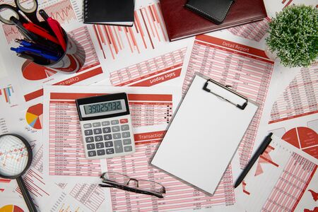 Business reports, blank paper sheet, data tables and charts - directly above view of office table workspace with place for text. Stock fotó