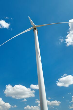 Electricity wind generator on bright cloudy sky background - wind energy and technology concept Banco de Imagens