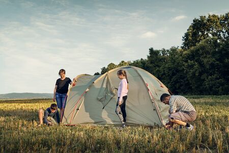 Family set up tent camp at sunset, beautiful summer landscape. Tourism, hiking and traveling in nature.