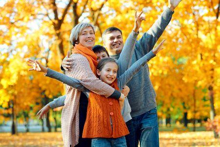 Szczęśliwa rodzina pozuje, bawi się i bawi się w jesiennym parku miejskim. Dzieci i rodzice wspólnie spędzają miły dzień. Jasne światło słoneczne i żółte liście na drzewach, sezon jesienny.