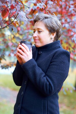 Beautiful woman posing with paper cup of tea or coffee in autumn city park, fall season 写真素材