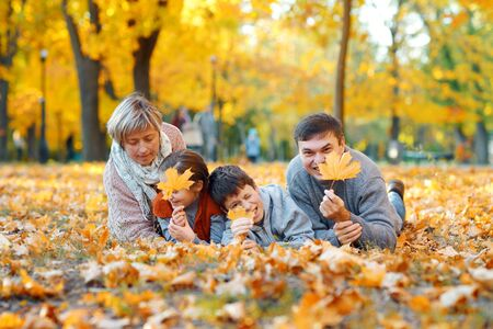 Happy family lying on fallen leaves, playing and having fun in autumn city park. Children and parents together having a nice day. Bright sunlight and yellow leaves on trees, fall season.