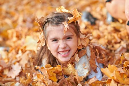 Happy child playing, posing, smiling and having fun in autumn city park. Bright yellow trees and leaves