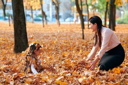 Famiglia felice in vacanza nel parco cittadino autunnale. Bambini e genitori che posano, sorridono, giocano e si divertono. Alberi e foglie giallo brillante