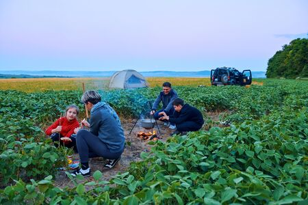 Family traveling and camping, twilight, cooking on the fire. Beautiful nature - field, forest and moon. 스톡 콘텐츠