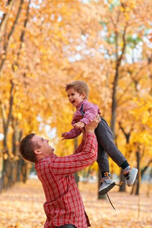 Happy family having holiday in autumn city park. Children and parents posing, smiling, playing and having fun. Bright yellow trees and leaves