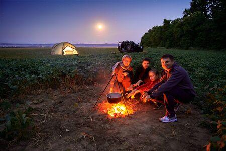 家族旅行やキャンプ、夕暮れ、火の上で調理。美しい自然 - フィールド、森、星と月。 写真素材