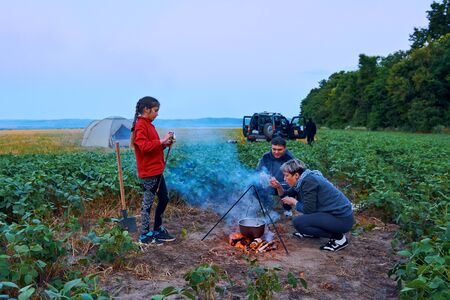 Family traveling and camping, twilight, cooking on the fire. Beautiful nature - field, forest and moon. Stok Fotoğraf