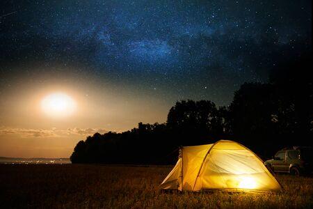 Reise- und Campingkonzept - Lagerzelt nachts unter einem Himmel voller Sterne. Orange beleuchtetes Zelt und Auto. Schöne Natur - Feld, Wald, Ebene. Mond und Mondschein
